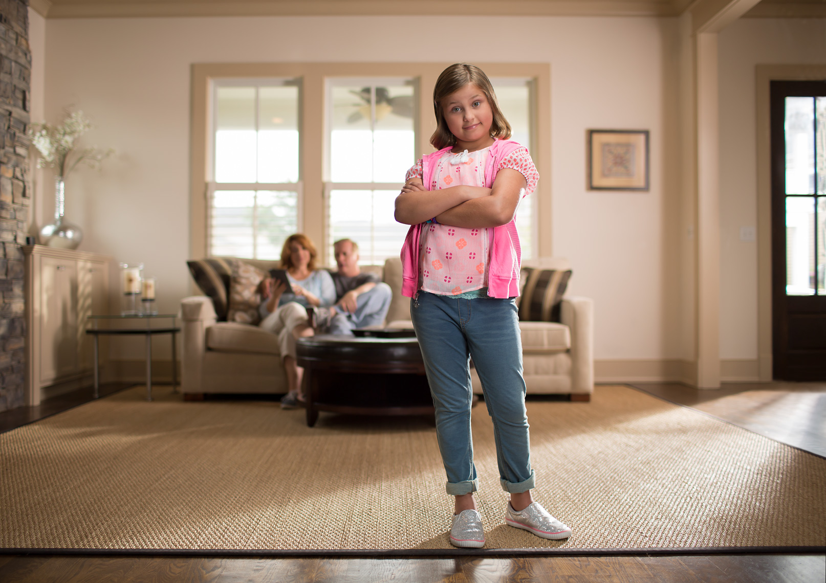 Kid in Living Room with Parents in Background